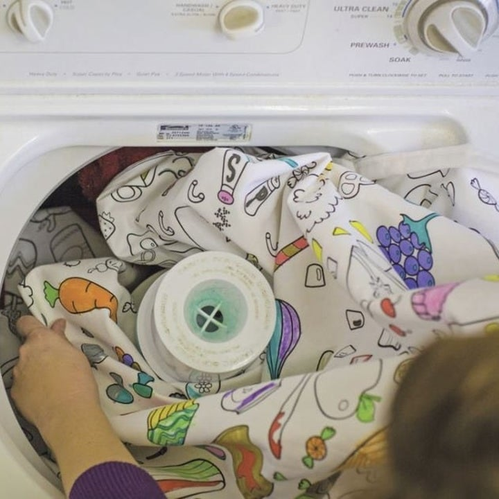 Person throwing colored tablecloth into washing machine