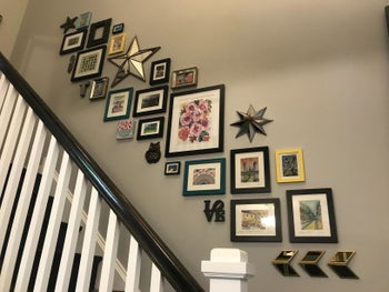 Reviewer's gallery wall of black frames hung using Command Strips