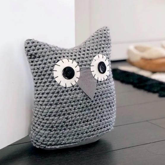 A knitted owl-shaped door stopper keeping a door open