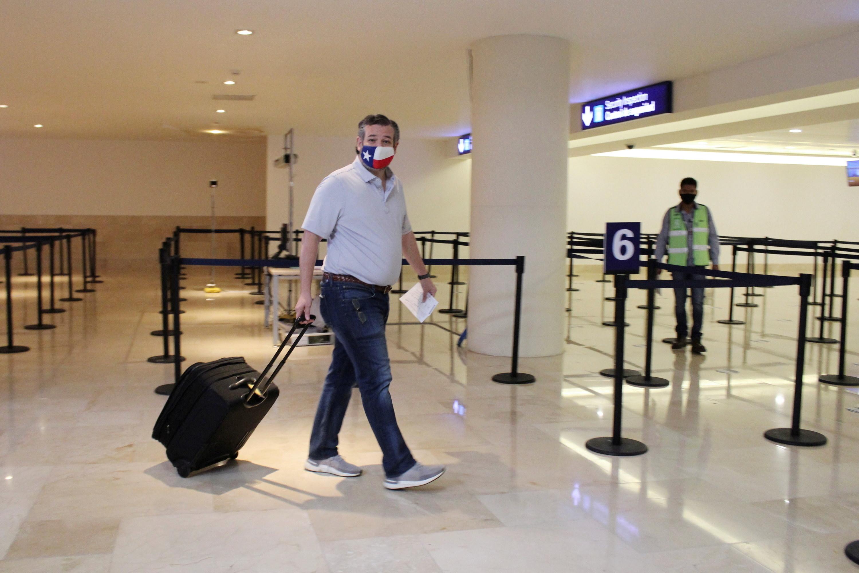 Ted Cruz wheels his luggage through an airport