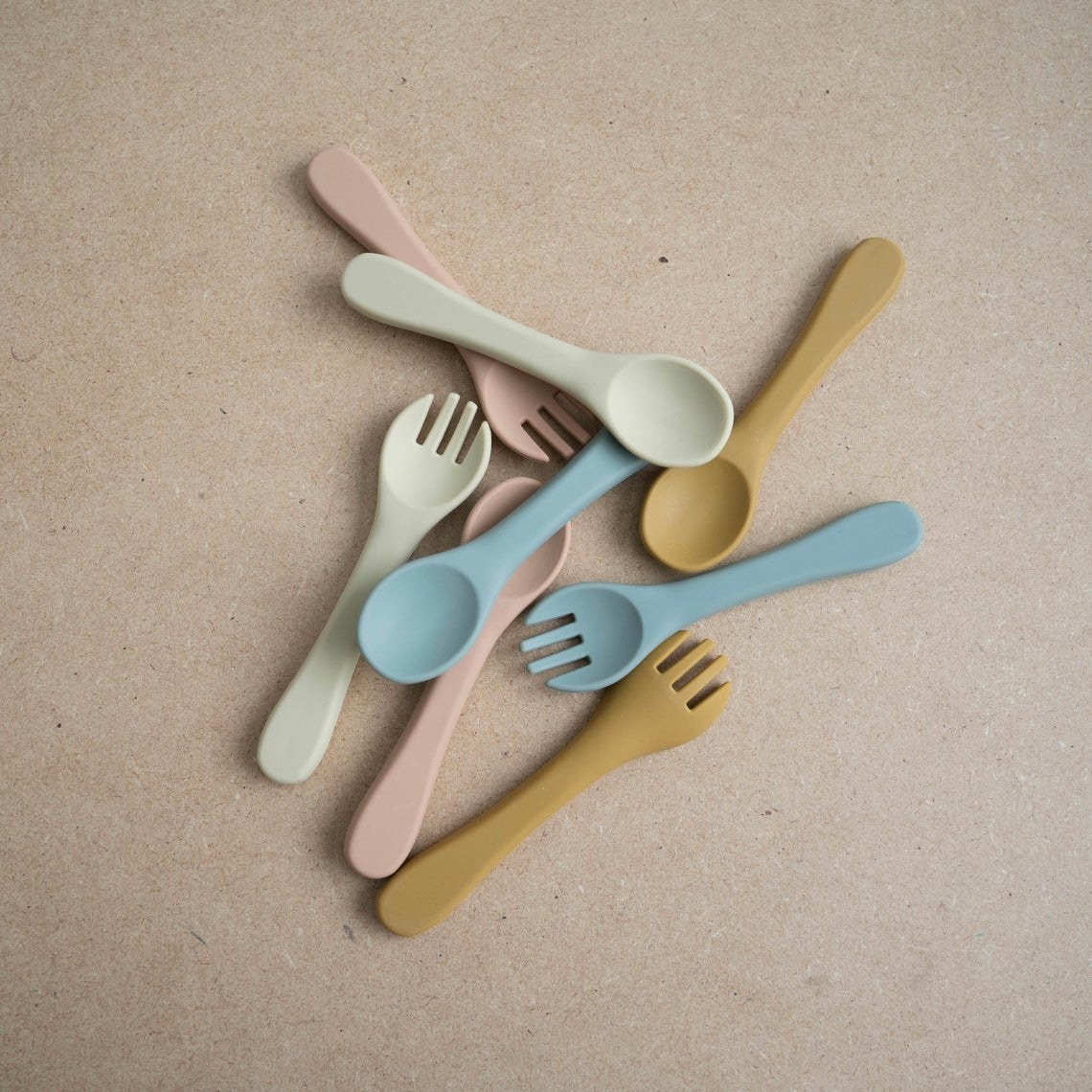 Several soft forks and spoons plopped together on a table