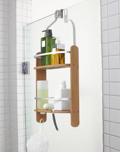 A shower caddy with bamboo sides hanging in a shower stall