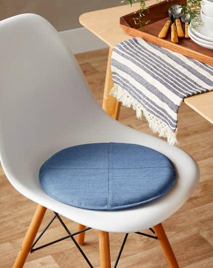 A circular denim cushion on a dining chair