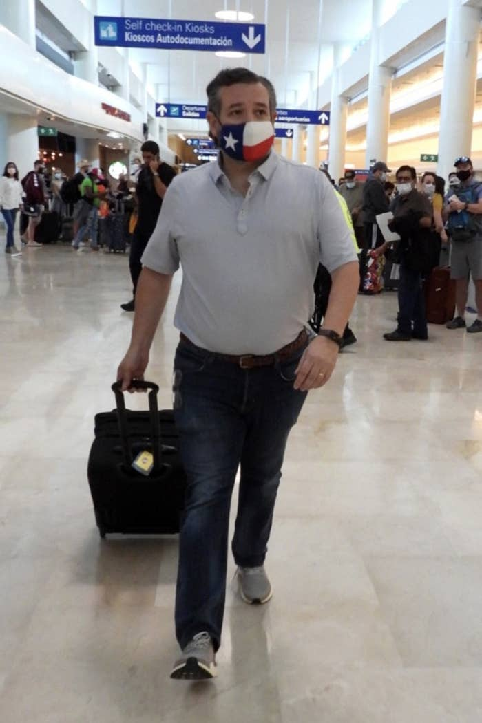 Ted walking through the airport while wearing a face mask with the Texas state flag printed on it