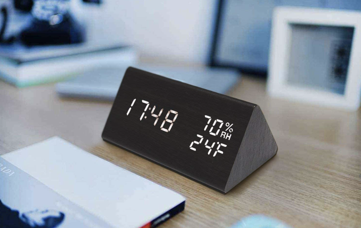 black digital alarm clock on a nightstand with a magazine and picture frame