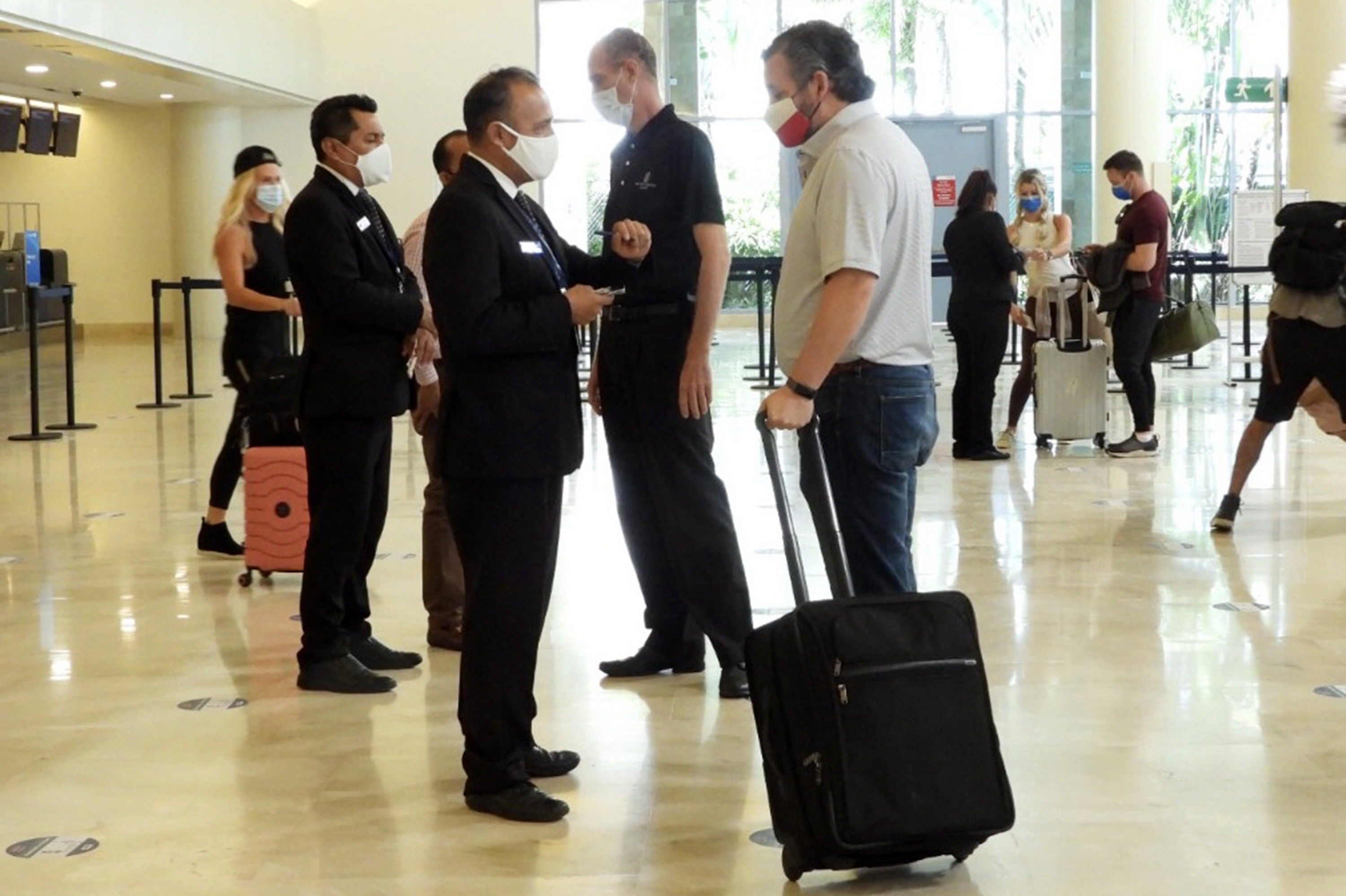 Ted Cruz talks to airport staff while wheeling his luggage