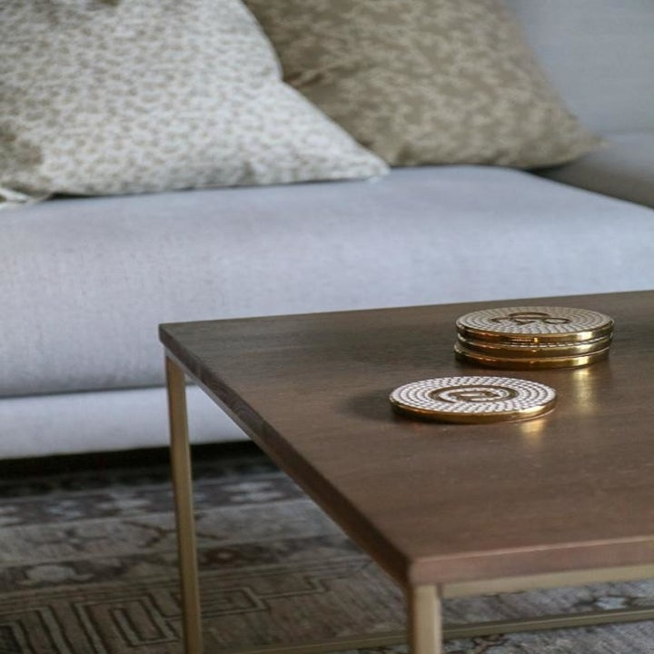 gold and white coasters with @ symbol on wooden table