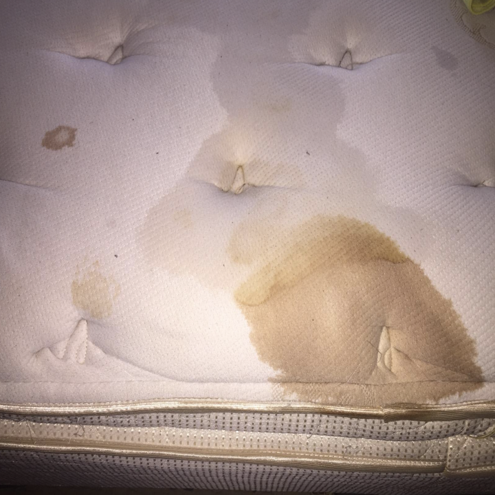 a reviewer's mattress with a big stain on it