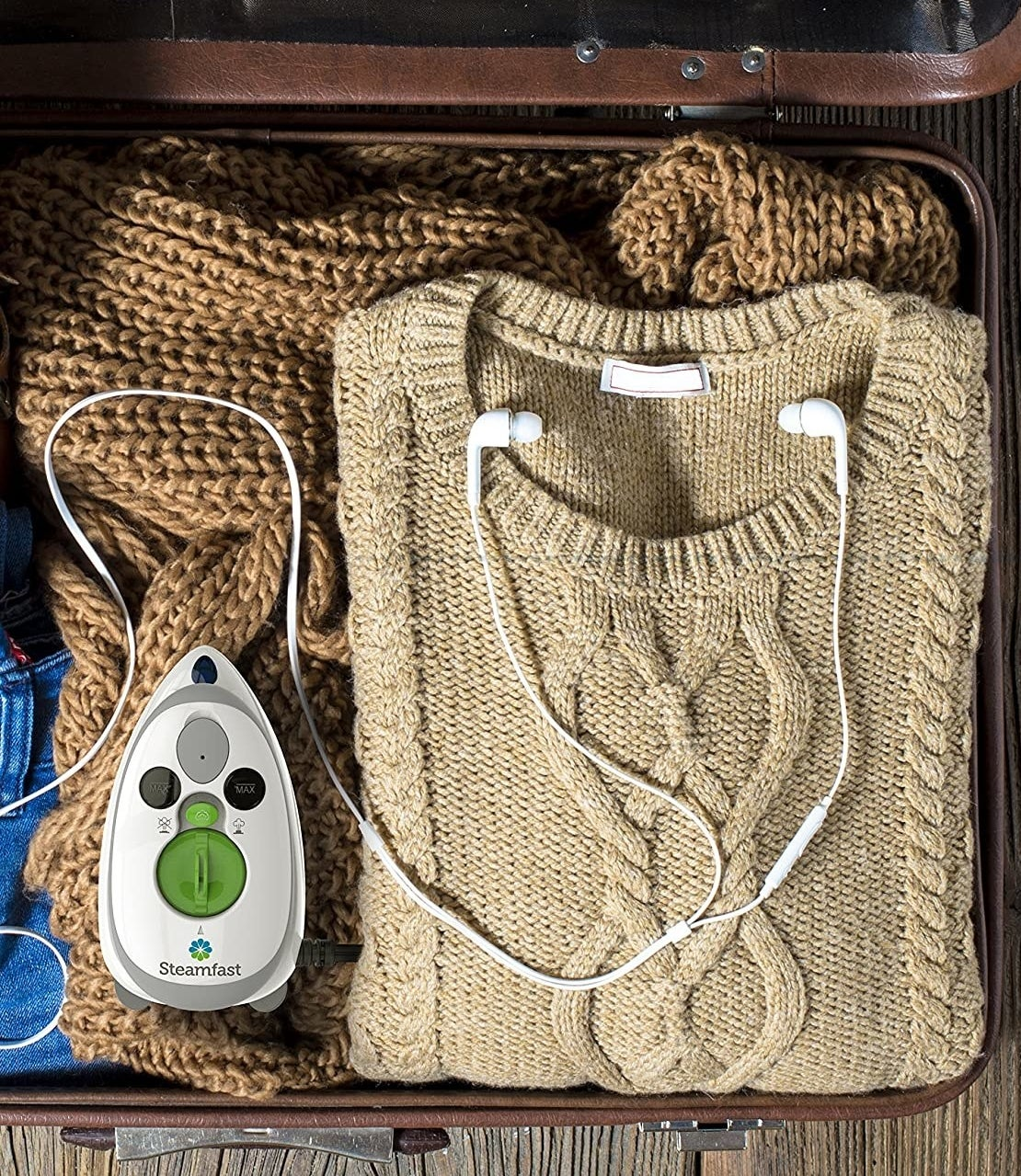 A flatlay of the tiny iron inside a suitcase next to a neatly folded sweater