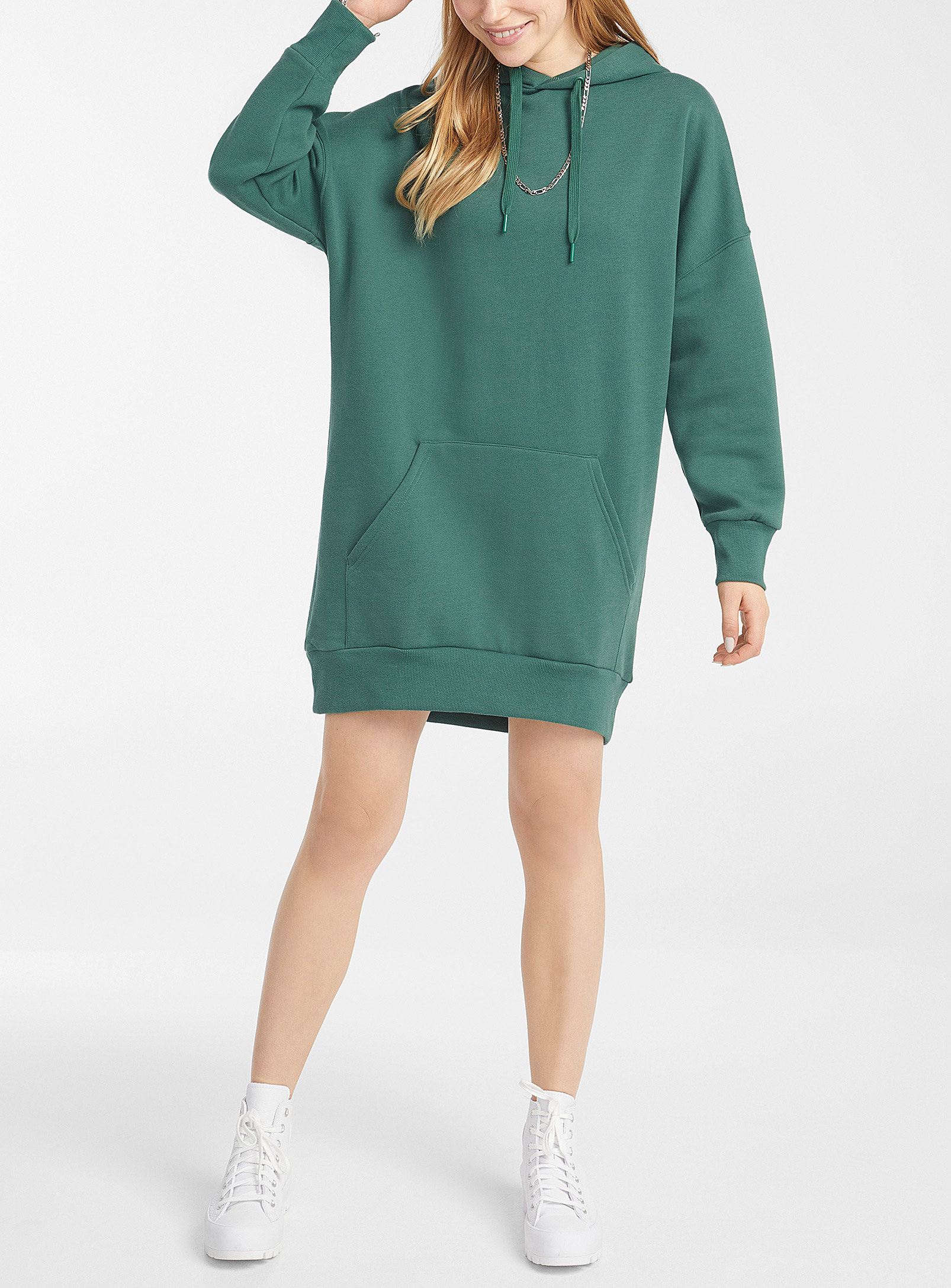 A person wearing a knee length sweatshirt dress