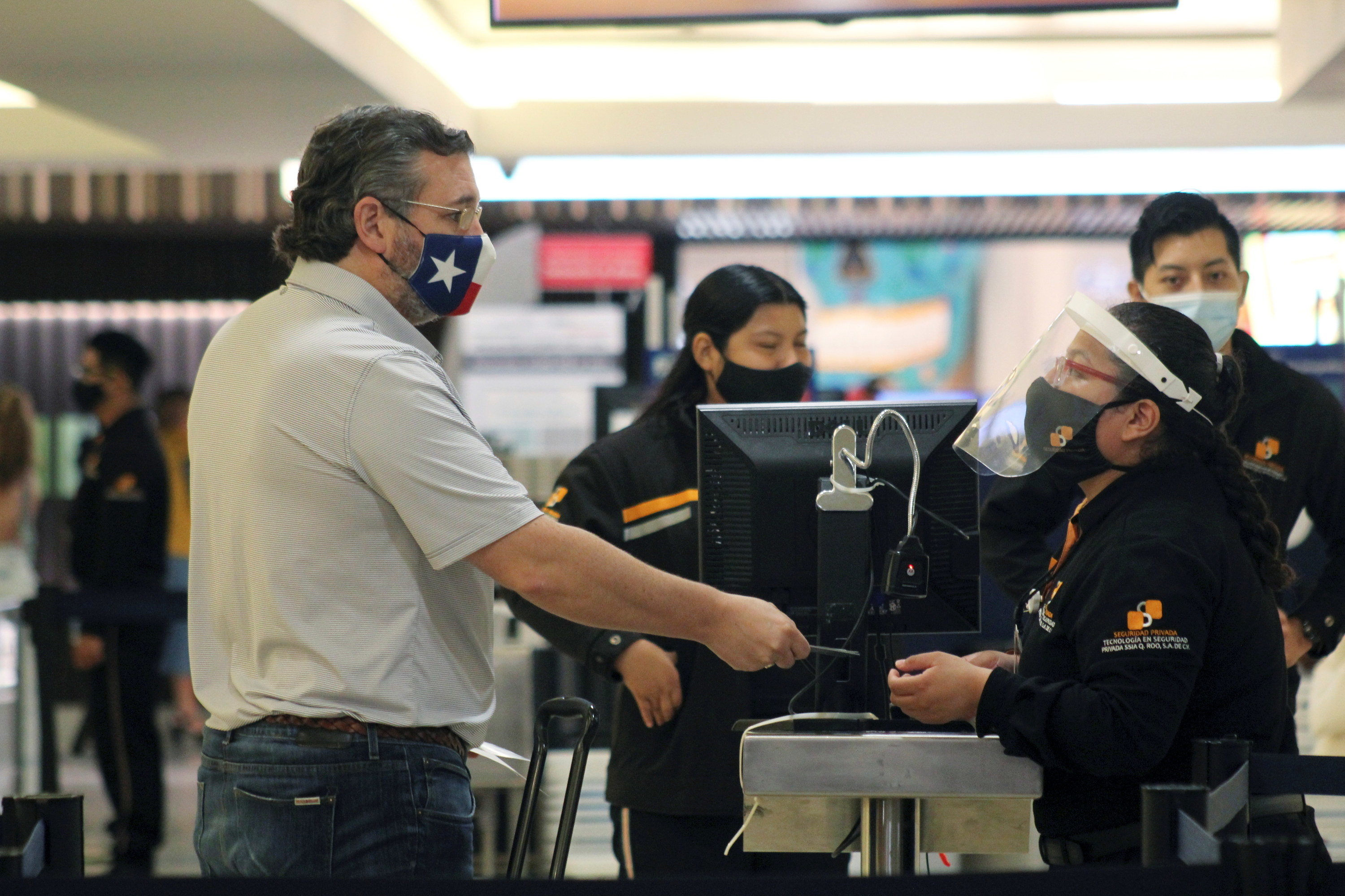 Ted Cruz talks to airport security guards wearing face coverings