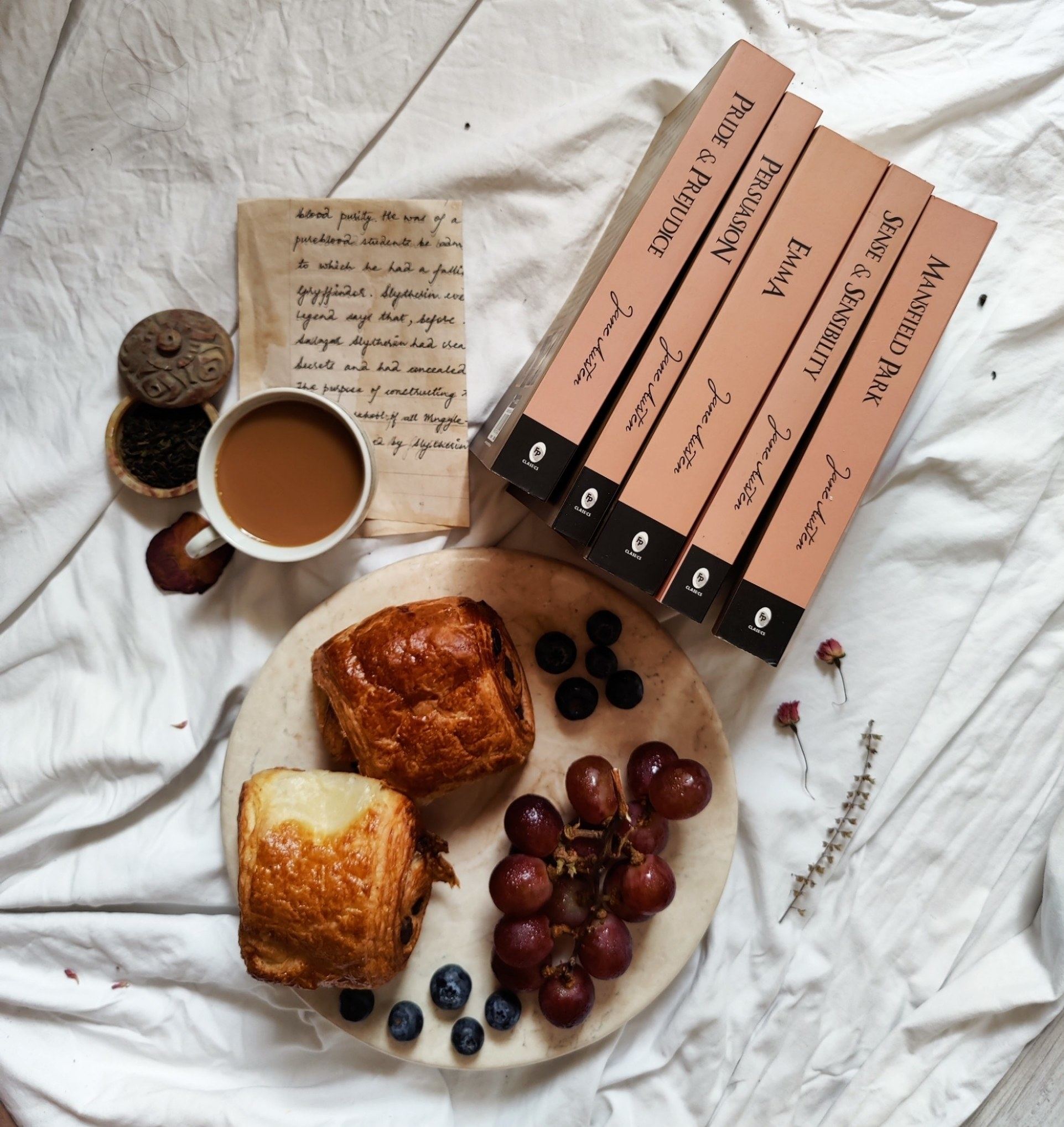 The book set pictured with a parchment, cup of coffee, bread rolls, grapes, and blueberries.