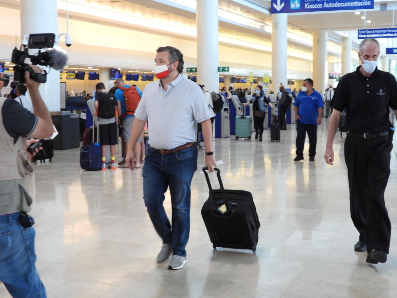 Ted Cruz wheels his luggage amid passengers and photographers
