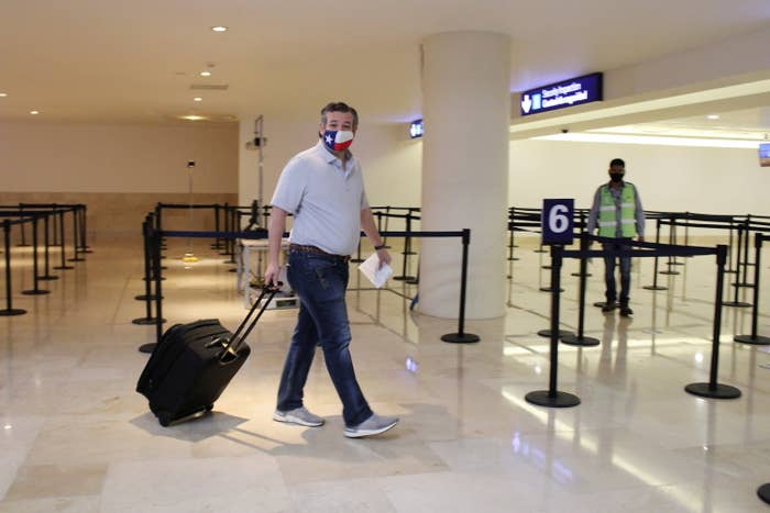 Ted Cruz wears a Texas flag mask as he pulls his luggage through Cancún International Airport