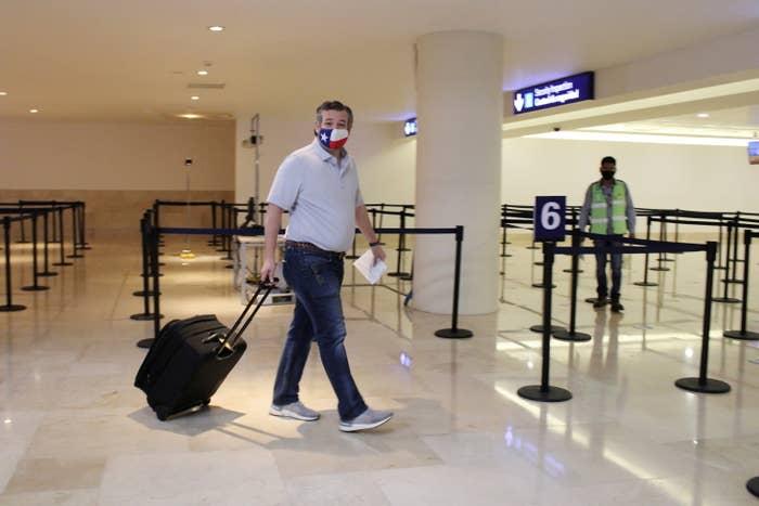 Ted Cruz wears a Texas flag mask as he pulls his luggage through Cancun International Airport