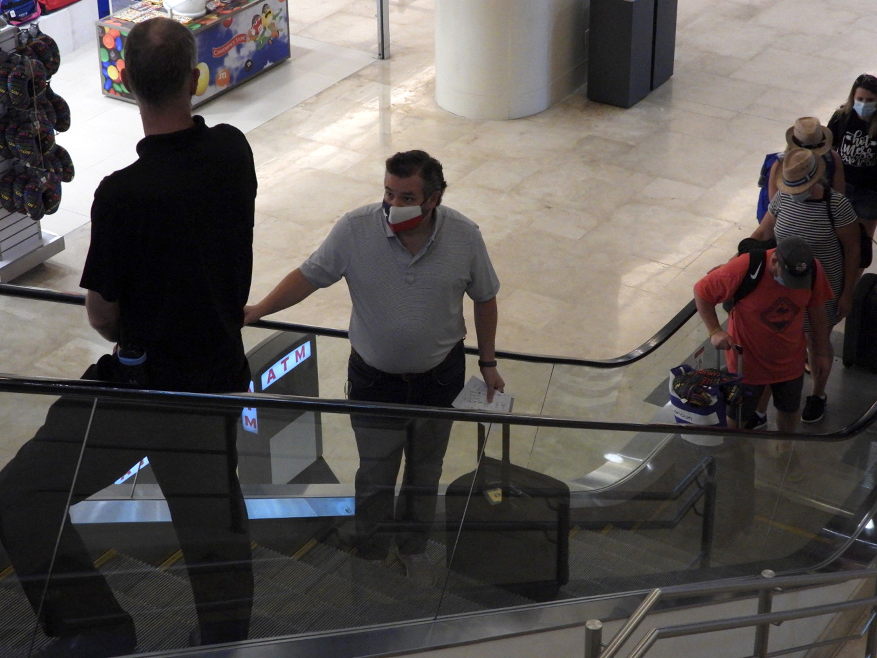Ted Cruz rides an escalator while holding his luggage handle