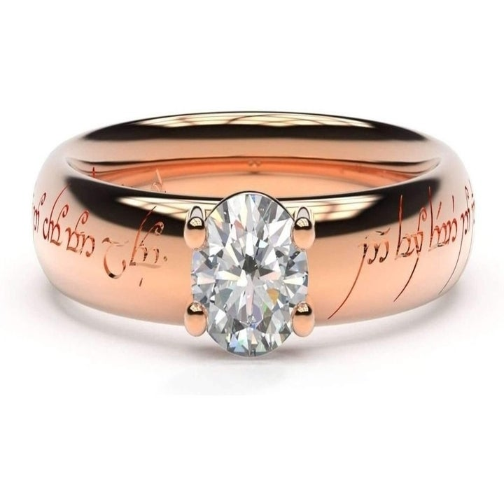 A rose gold band engraved with Elvish script and a single diamond