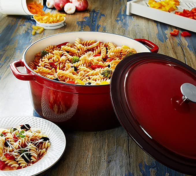 Maroon enamel covered Dutch oven with pasta in it.