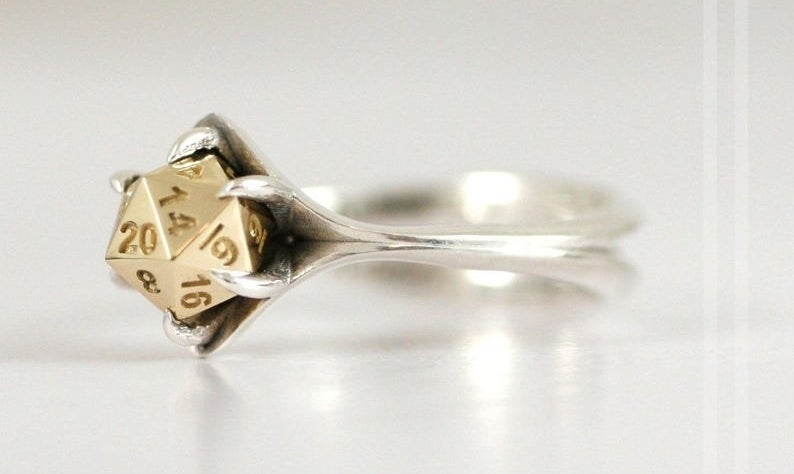 A silver band with a gold center shaped to look like a D20 dice
