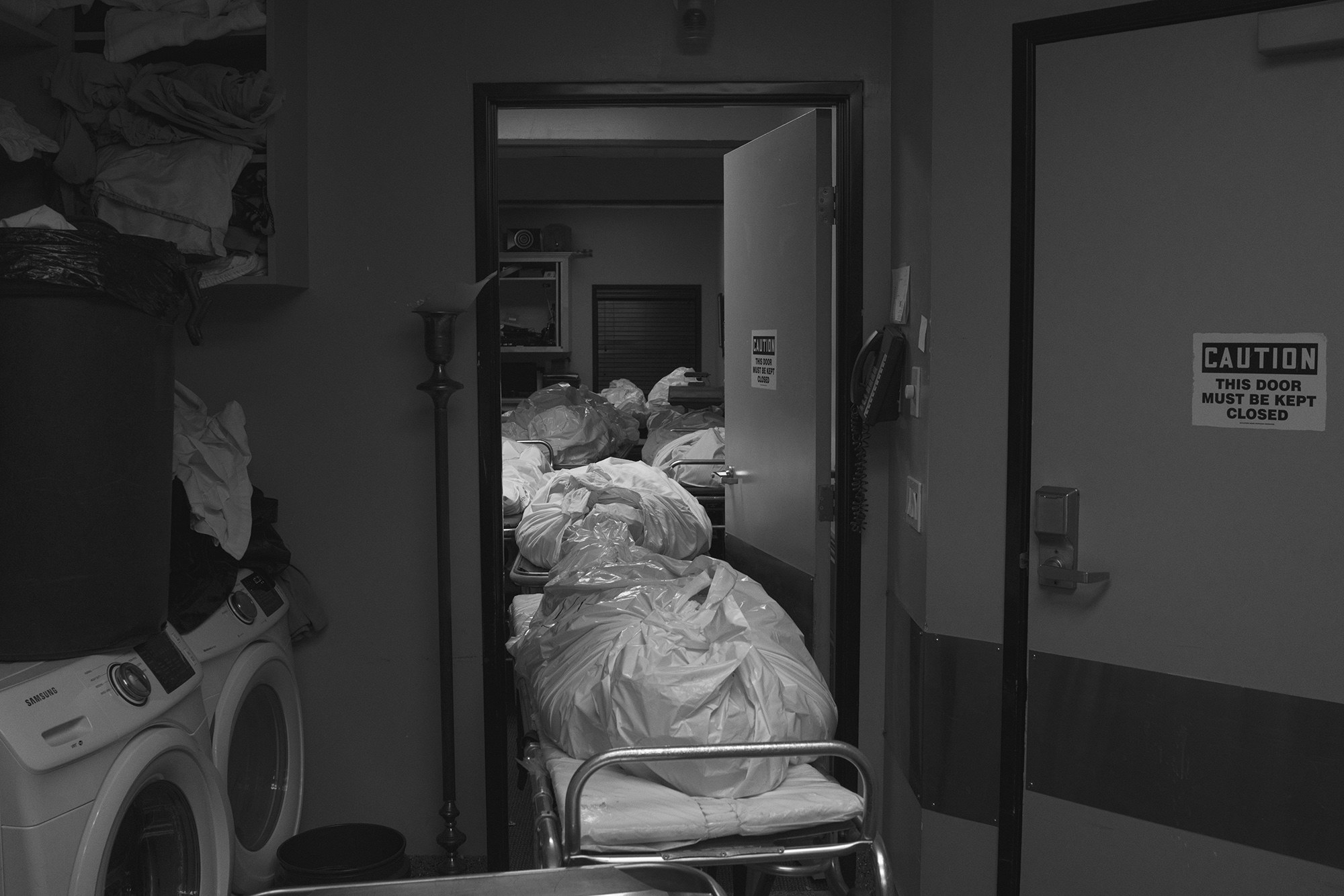 Many bodies are seen on gurneys in a hallway
