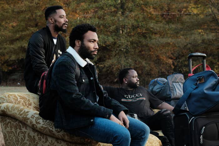 Lakeith Stanfield, Donald Glover, and Brian Tyree Henry sit on a couch in the TV show Atlanta