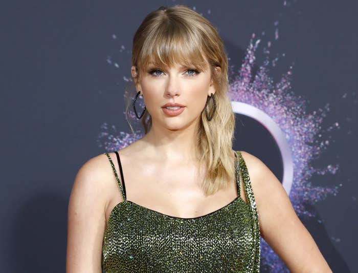 Taylor makes a straight face while posing on a red carpet in a sparkly green dress