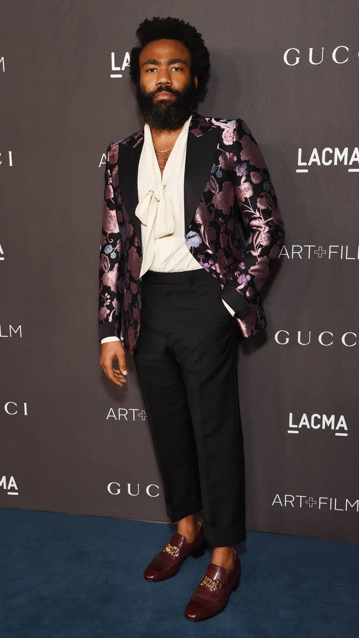 Donald Glover at a gala in Los Angeles in November 2019 wearing a floral patterned blazer and a flow-y blouse