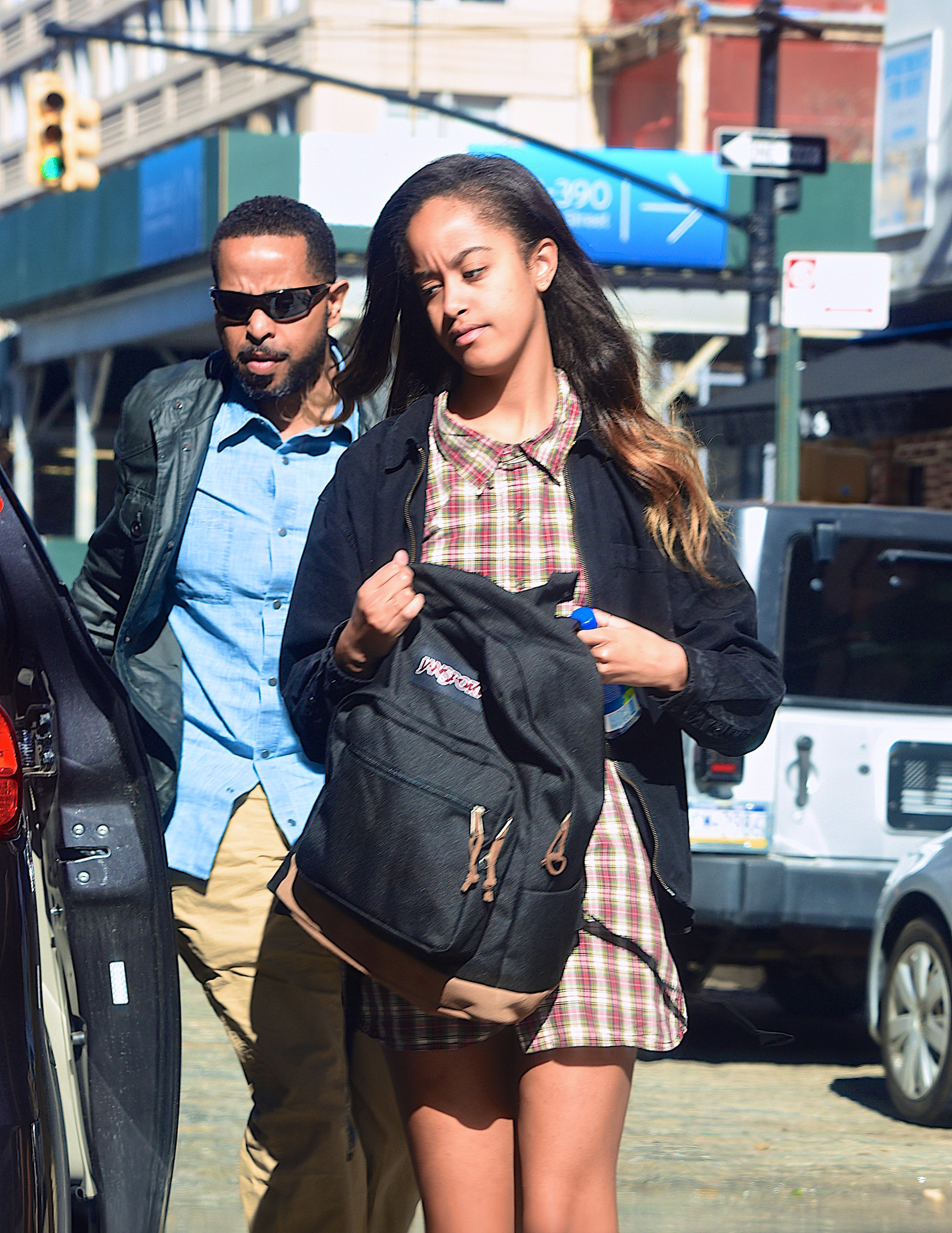 Malia Obama walks in Manhattan in 2017 wearing a flannel-print collared dress and jacket while carrying a backpack in her hands
