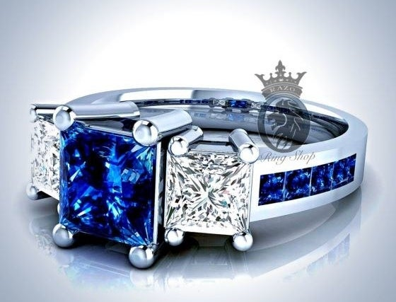 A ring with a center blue sapphire flanked by two square white diamonds and a band encrusted with smaller. blue sapphires