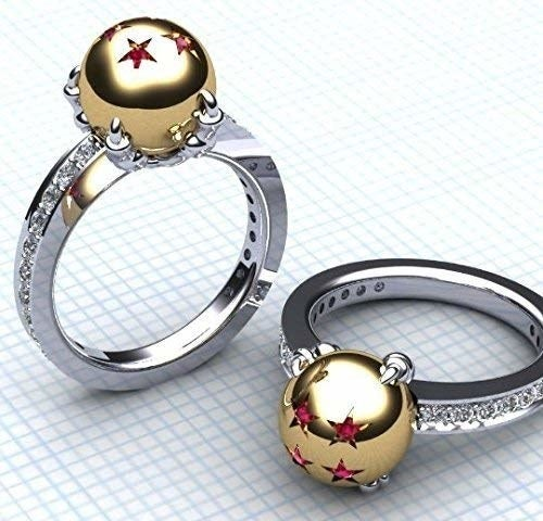 A pair of matching rings with a diamond-encrusted band and a gold ball encrusted with ruby stars