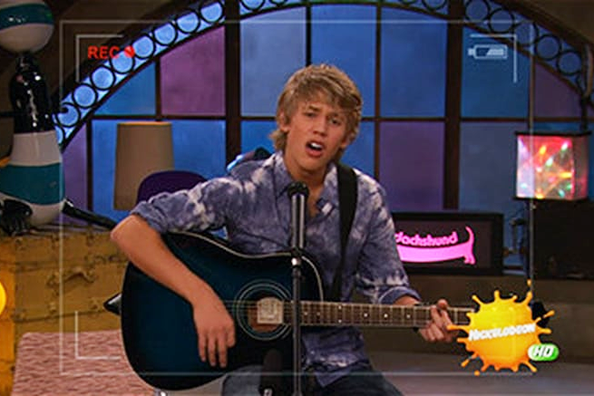 Austin Butler plays guitar and sings during an iCarly web show