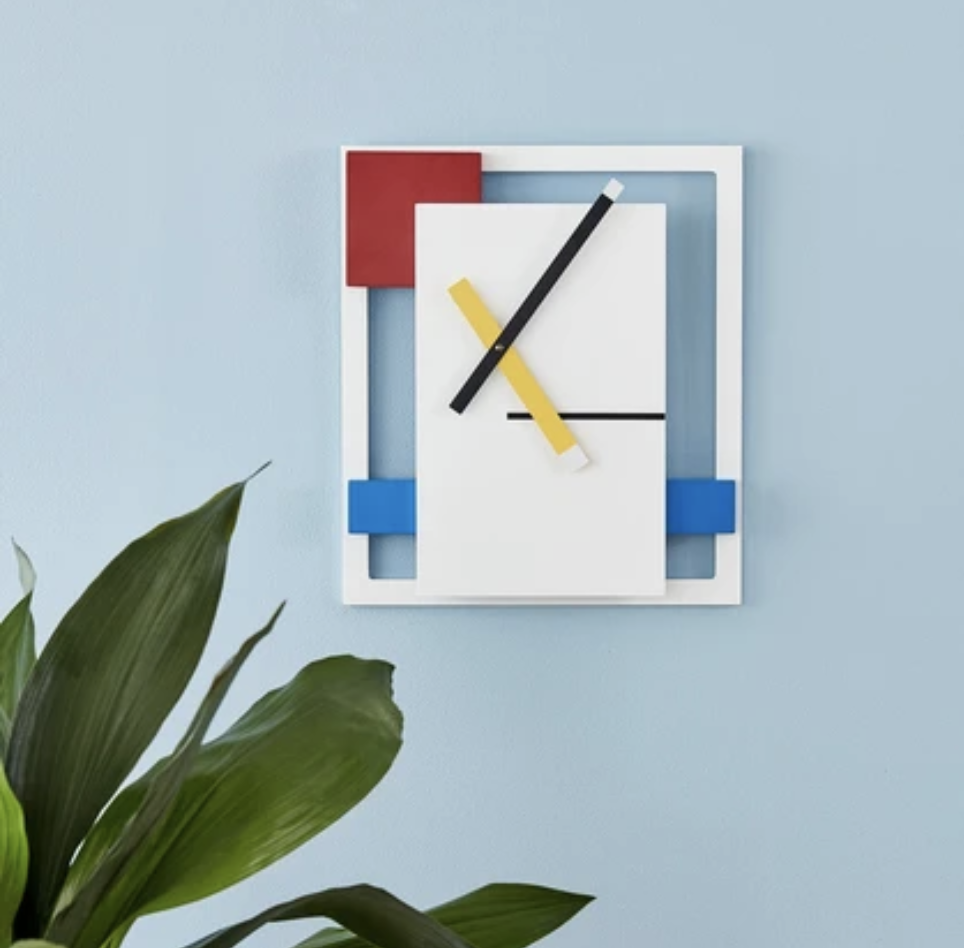 A decorative rectangle wall clock with yellow, red, and blue accents