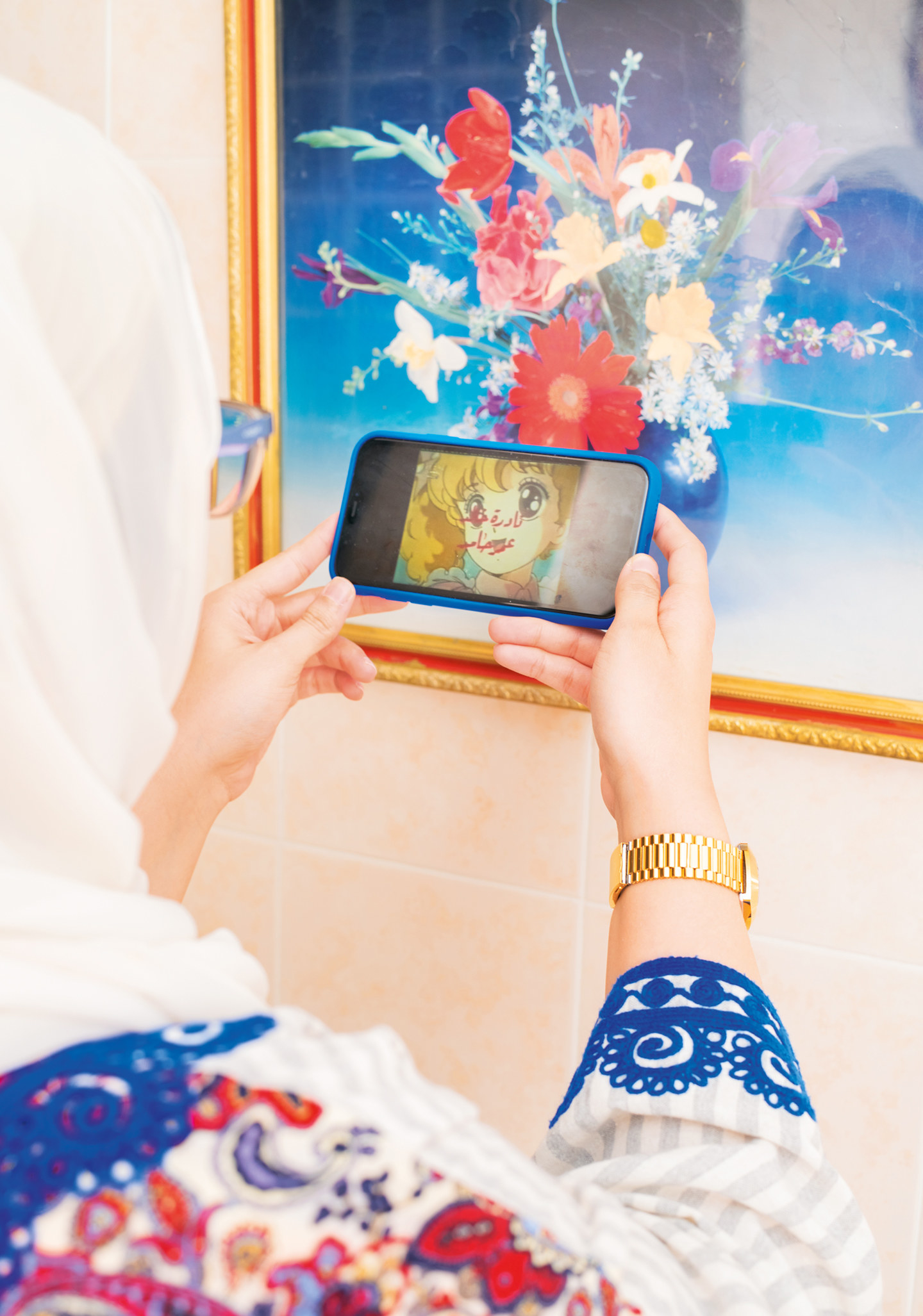 A woman holding up a phone with anime playing on the screen