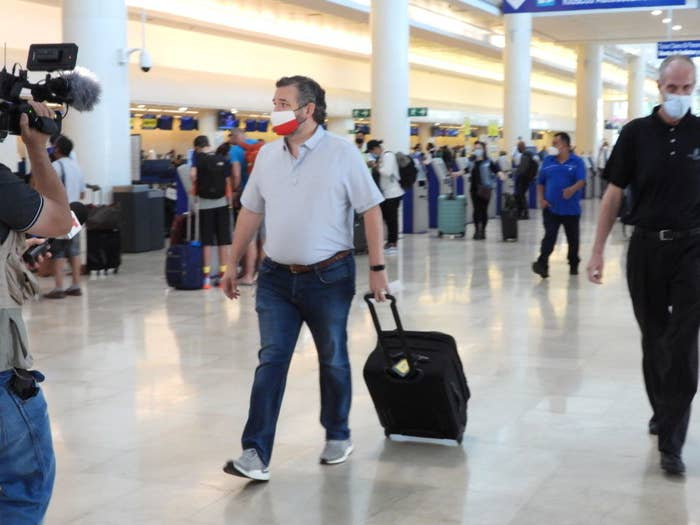 Ted Cruz wheeling his suitcase as he walks through an airport to go to Mexico while the state of Texas is in crisis