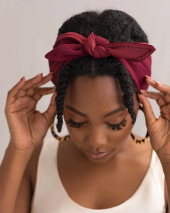 model with kinky hair wearing the bandie in red
