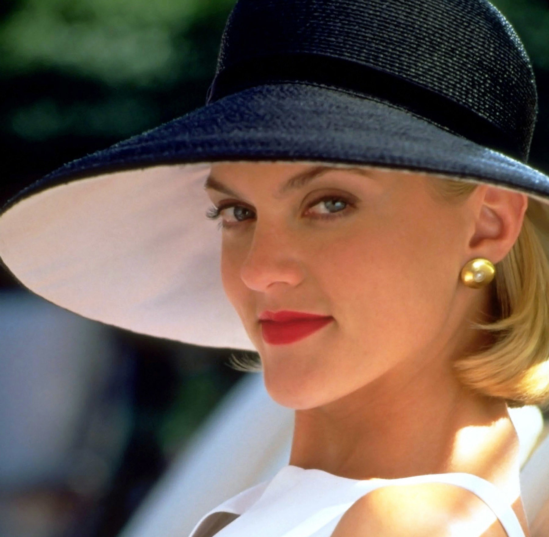Photo of Meredith smirking while wearing a large black hat