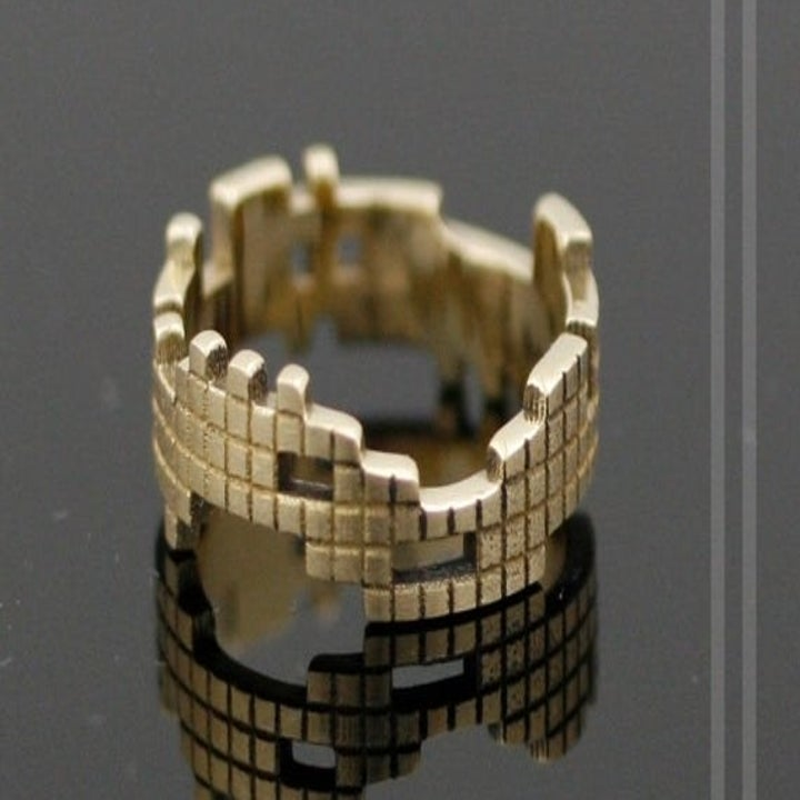 an asymmetrical gold band etched to look like different-shaped Tetris blocks