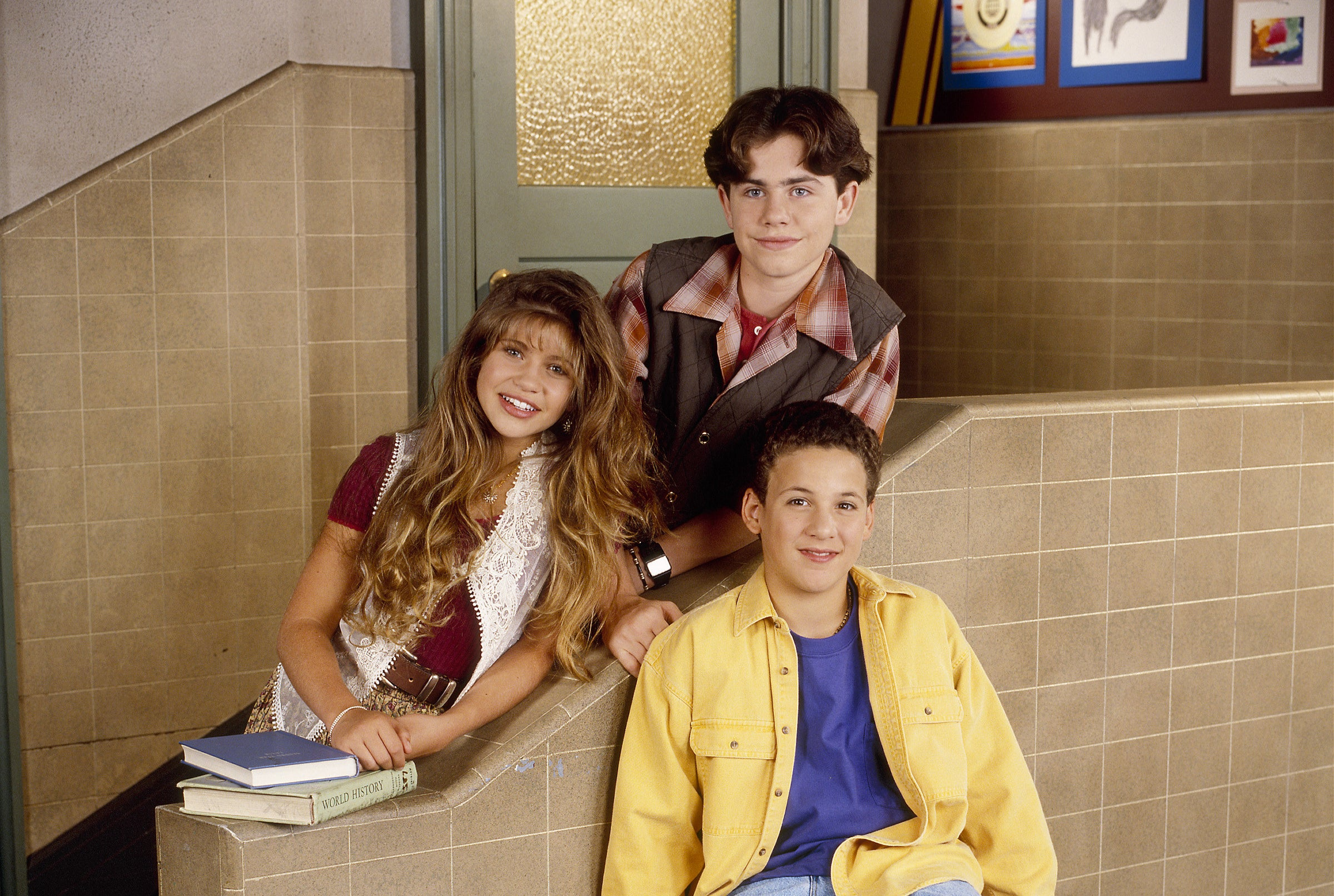 Season 2 photo of Danielle Fishel, Rider Strong, and Ben Savage posing on the school's staircase