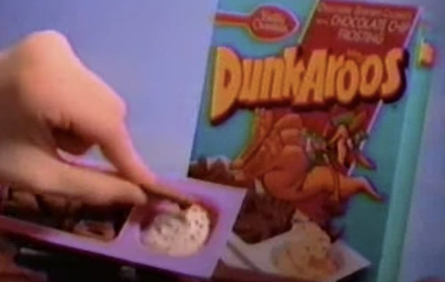 A screenshot of a kid's dipping into a cookie into the Dunkaroos cream