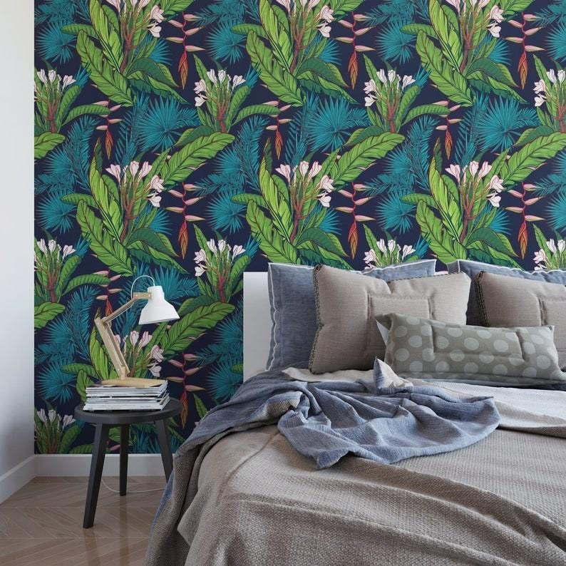 blue, green, and pink banana leaf-print adhesive wallpaper next to bed