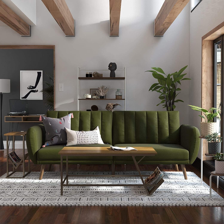 green convertible velvet futon in front of patterned carpet