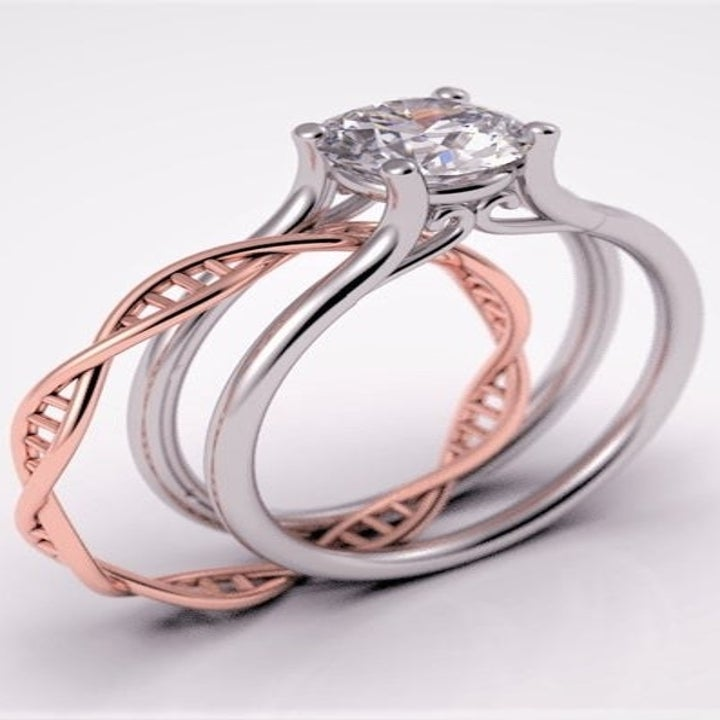 A silver ring with a single diamond and a split band with a rose gold band that looks like DNA partially inserted into the band