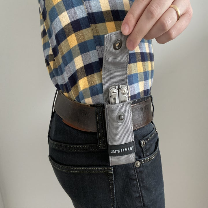 Reviewer showing Leatherman sheath opened and attached to belt