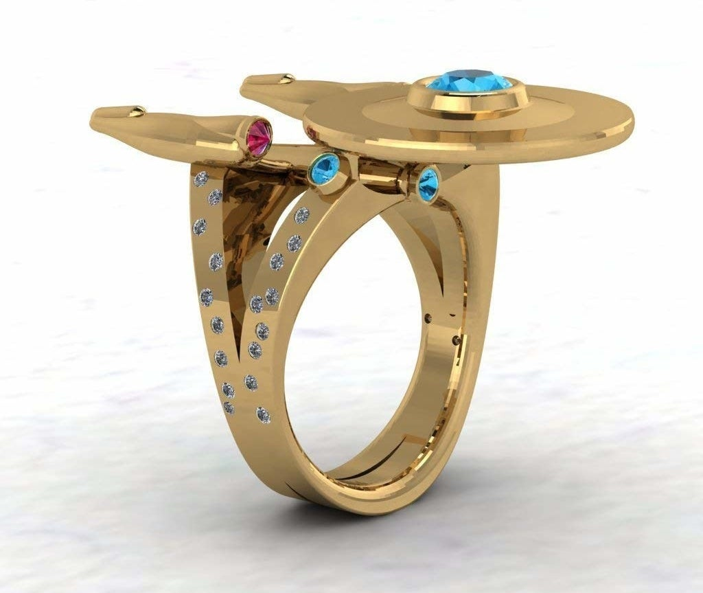 """A gold ring with a diamond-encrusted band and a top shaped like Starship Enterprise from """"Star Trek"""" accented with red and blue gemstones"""