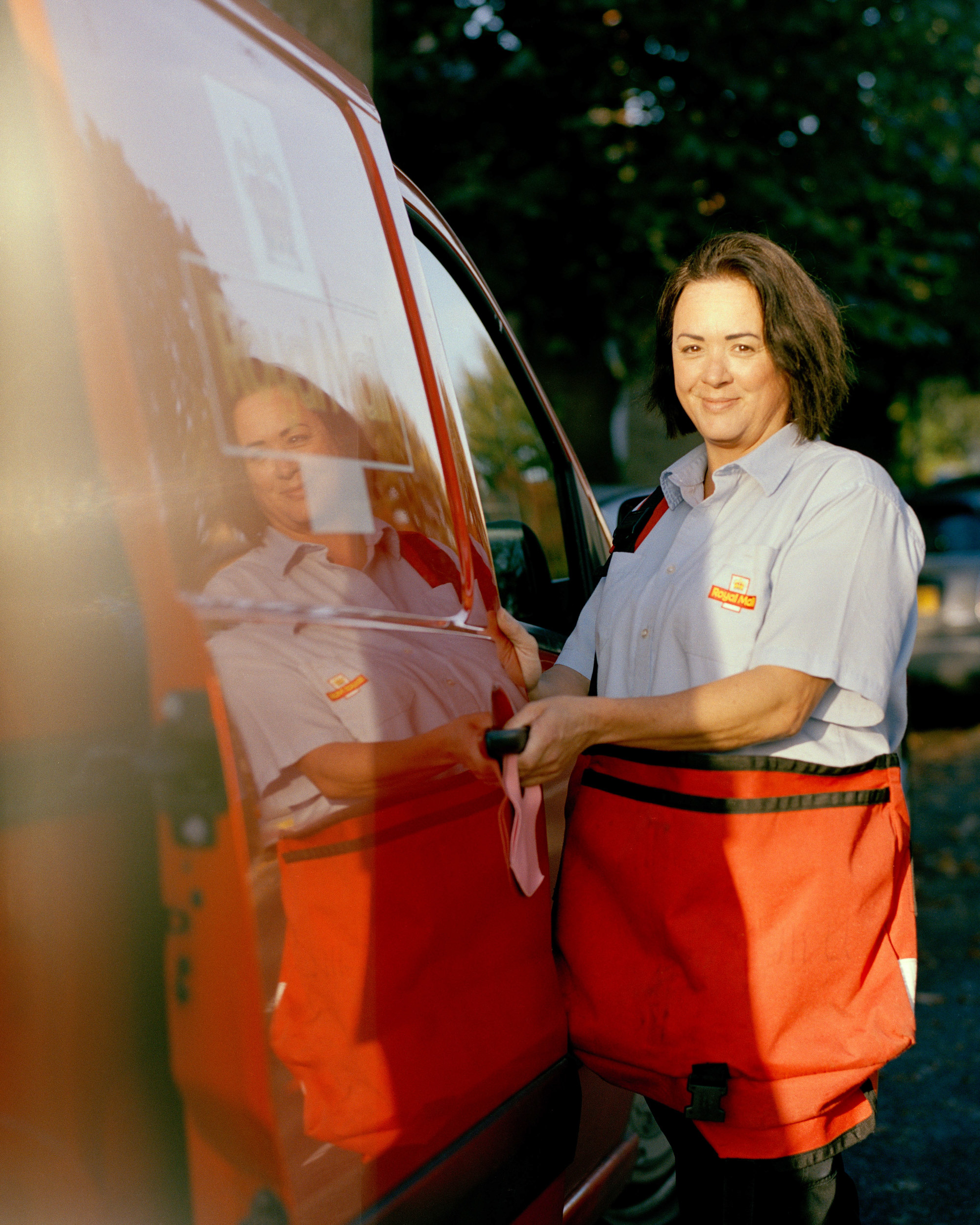 A woman postal work in the United Kingdom standing next to her truck