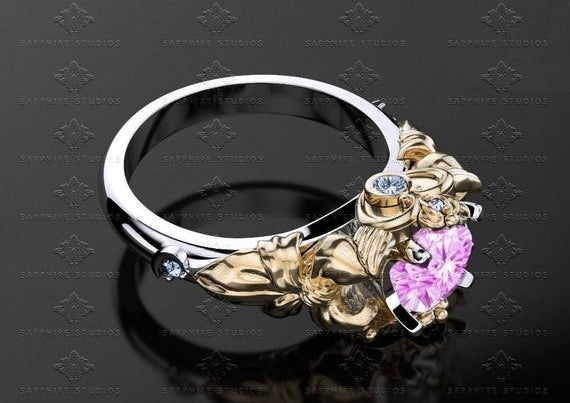 A silver band with an etched gold setting and a pink saphire