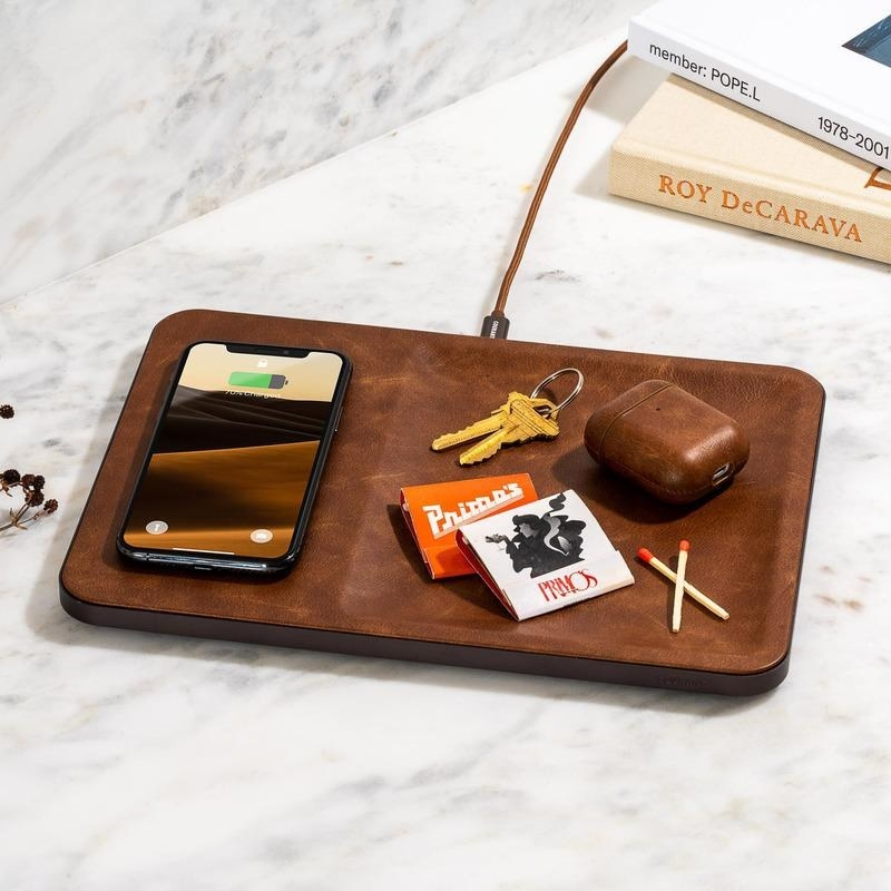 brown Catch3 Wireless Charger with a smartphone and a carrying tray for keys and an AirPod case