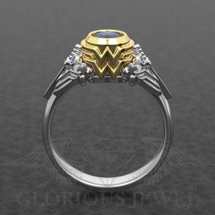 A silver ring with a blue center gemstone with a gold setting shaped to look like the Wonder Woman symbol