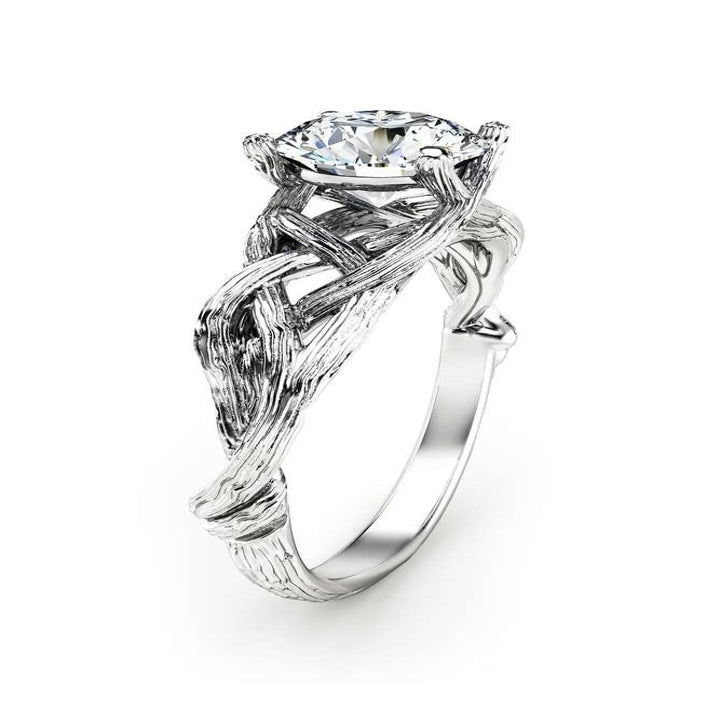 A profile view of a silver moissanite ring with a band designed to look like intertwining branches