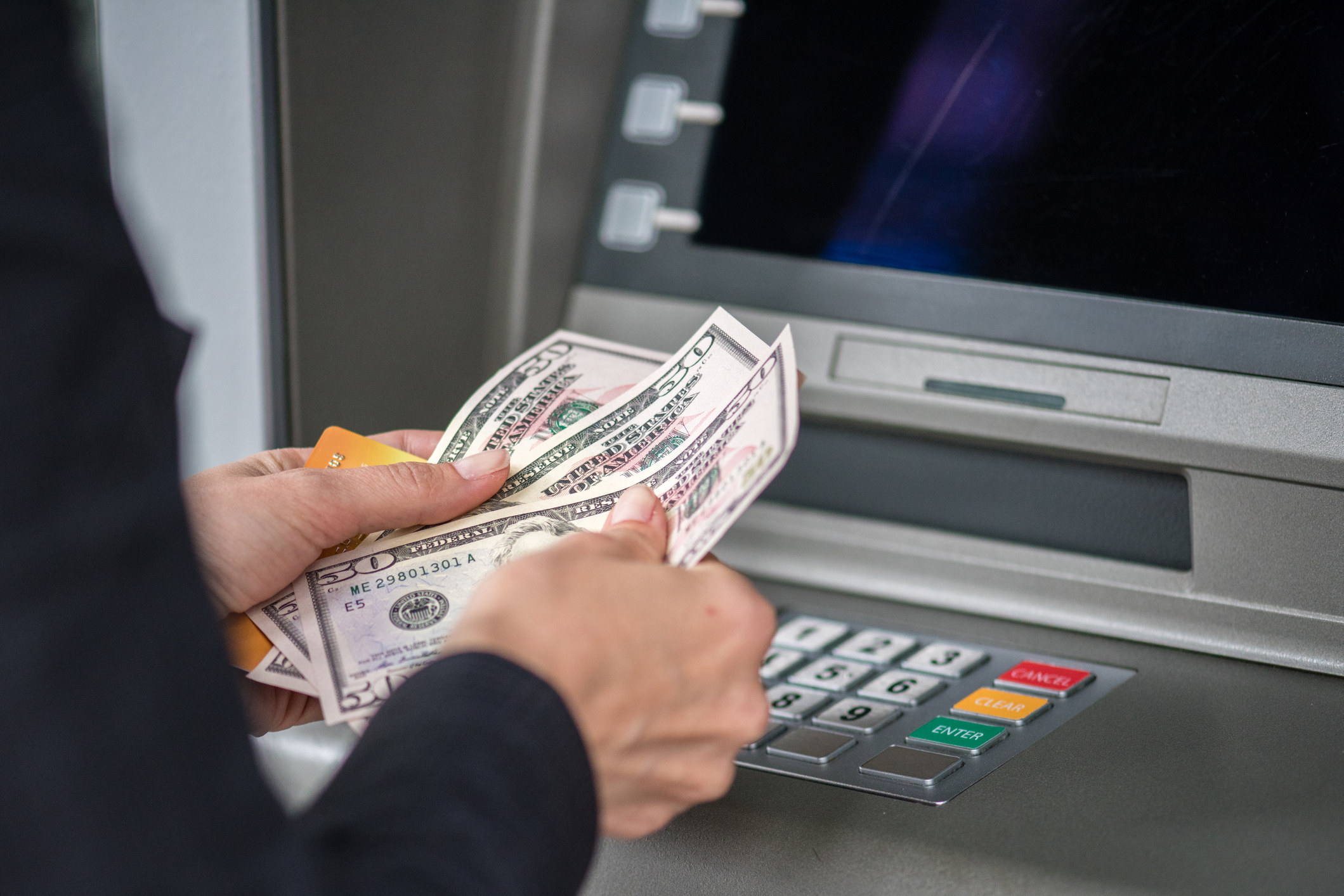 Woman counting cash at ATM